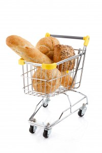 Shopping trolley full of bread and rolls on white background